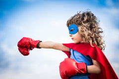 Superhero kid. Against dramatic blue sky background Royalty Free Stock Photography