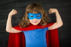 Superhero kid. Against school blackboard royalty free stock images