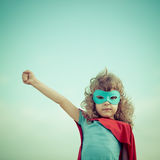 Superhero kid. Against summer sky background. Girl power and feminism concept Royalty Free Stock Image