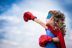 Superhero kid. Against summer sky background. Girl power and feminism concept Stock Photo