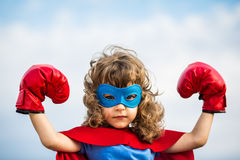 Superhero kid. Girl power concept. Superhero kid wearing boxing gloves against blue sky background. Girl power and feminism concept