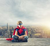 Superhero kid sitting on a wall that dreams royalty free stock image