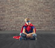 Superhero kid sitting on a wall that dreams royalty free stock photography