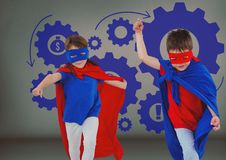 Superhero kids with blank grey background and blue settings cogs icons. Digital composite of Superhero kids with blank grey background and blue settings cogs Royalty Free Stock Photography