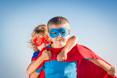 Superhero kids. Superhero children against summer sky background. Kids having fun outdoors. Boy and girl playing. Success and winner concept royalty free stock photography