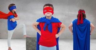 Superhero kids in grey room Royalty Free Stock Photo