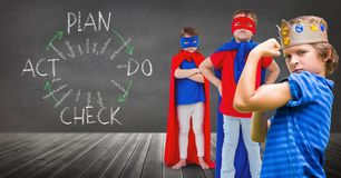 Superhero kids and king crown boy with blackboard background and plan graphics. Digital composite of Superhero kids and king crown boy with blackboard background Royalty Free Stock Photo