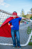 Superhero leaning on football goal. Boy dressed in cape and mask leaning on football goal royalty free stock images