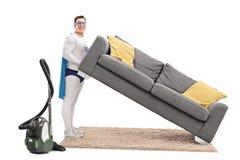 Superhero lifting a sofa and vacuuming royalty free stock image