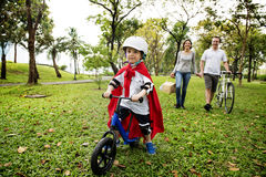 Superhero little boy riding bicycle with family in the park Royalty Free Stock Photos