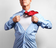 Superhero. Mature businessman tearing his shirt off over white b Stock Image