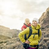 Superhero mother with little boy travelling in backpack Stock Photo