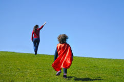 Superhero mother show her daughter how to be  a superhero. Against blue sky background with copy space. concept photo of Super hero, girl power, play pretend Stock Photography