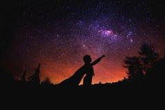 Superhero på den stjärnklara himmelbakgrunden för natt Blandat massmedia fotografering för bildbyråer