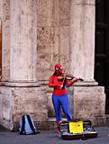 Superhero playing violin in the streets of Rome. Anonym violin player in the streets of Rome. Superhero musician. Italy royalty free stock image