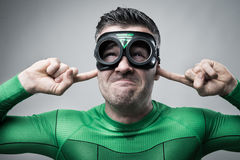 Superhero plugging ears with fingers Royalty Free Stock Image