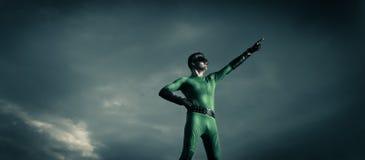 Superhero pointing with dramatic background Stock Photos