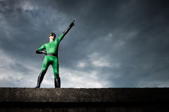 Superhero pointing with dramatic background Royalty Free Stock Photo