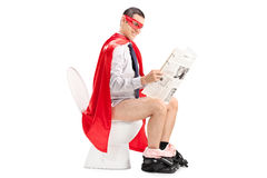 Superhero reading the news seated on a toilet Stock Photo