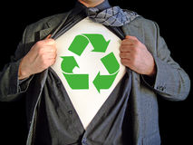 Superhero recycle. A business man isolated against a black background tearing open his shirt to reveal a recycle sign on a t shirt stock images