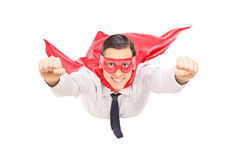 Superhero with red cape flying Stock Photo