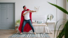 Superhero in red cape and mask dancing in bedroom at home having fun. Superhero in red cape and mask is dancing in bedroom at home having fun enjoying music and stock video