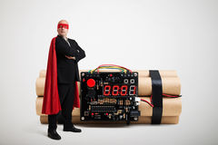 Superhero in red cloak and mask standing near big bomb Stock Images