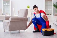 The superhero repairman with tools in repair concept Stock Photo