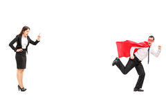 Superhero running away from angry businesswoman Stock Images