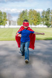 Superhero running forward. Boy dressed in cape and mask running forward and jumping up royalty free stock photo