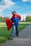 Superhero running forward and jumping. Boy dressed in cape and mask running forward and jumping stock images