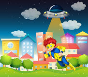 A superhero and a saucer near the buildings Royalty Free Stock Photography