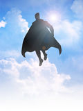 Superhero. Silhouette of a superhero figure flying on clouds Royalty Free Stock Photography