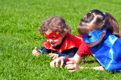Superhero sisters play outdoors. stock photo