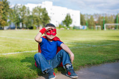 Superhero sitting and looking from under his hand. Boy dressed in cape and mask sitting on grass and looking from under his hand Royalty Free Stock Photography