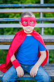 Superhero sitting on sport tribune. Boy dressed in cape and mask sitting on sport tribune stock images
