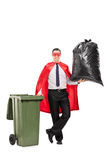 Superhero som rymmer en stor avfallpåse Arkivfoton