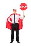 Superhero som rymmer ett stopptecken Royaltyfri Foto