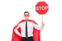Superhero som rymmer ett stopptecken Arkivbild