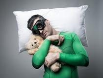 Superhero som sover på en kudde som svävar i luften Arkivfoton