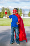 Superhero standing with arm raised. Boy dressed in cape and mask standing with his arm raised stock images