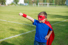 Superhero standing with arm raised and calling Stock Image