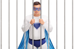 Superhero standing behind bars in a prison Stock Photo