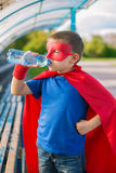 Superhero standing and drinking water from a bottle. Boy dressed in cape and mask standing and drinking water from a bottle Stock Photos