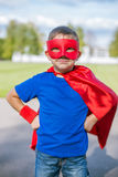Superhero standing with hands on hips. Boy dressed in cape and mask standing with hands on hips stock images