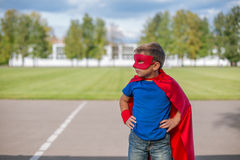 Superhero standing with hands on hips and looking sideways. Boy dressed in cape and mask standing with hands on hips and looking sideways stock photography