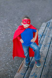 Superhero standing with hands on hips and looking up. Boy dressed in cape and mask standing with hands on hips and looking up stock images