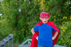 Superhero standing with hands on hips and smiling. Boy dressed in cape and mask standing with hands on hips and smiling stock image