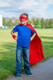 Superhero standing and looking towards. Boy dressed in cape and mask standing with hands on hips and looking towards Stock Photography