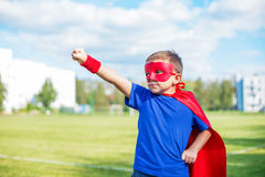 Superhero standing with raised arm and calling up. Boy dressed in cape and mask standing with his arm raised and calling up royalty free stock photo